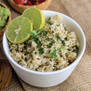Cilantro lime brown rice in a white bowl with fresh limes