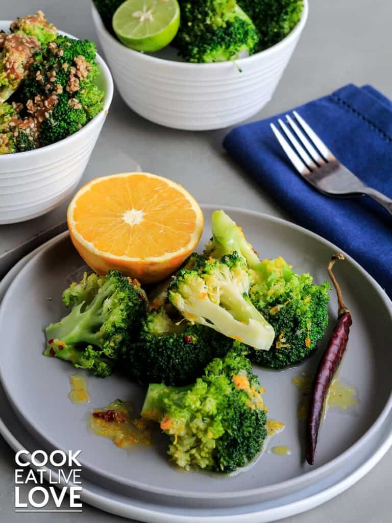 Broccoli on a plate with orange and chile garnish