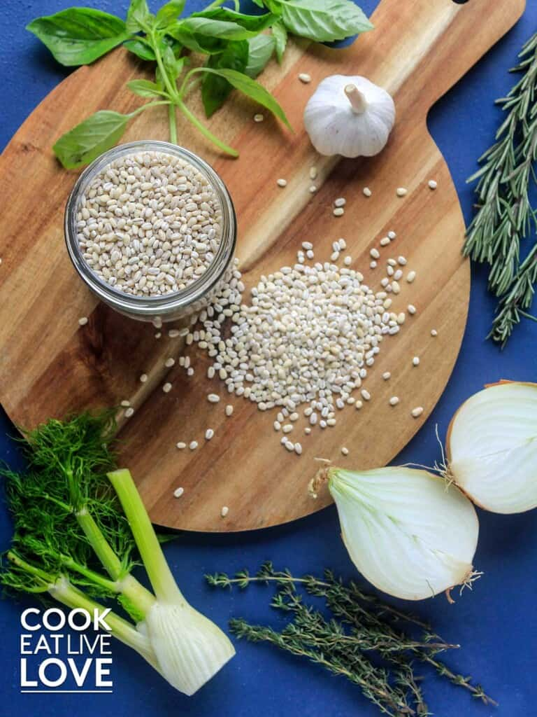 Uncooked barley on a cutting board with other ingredients around it.