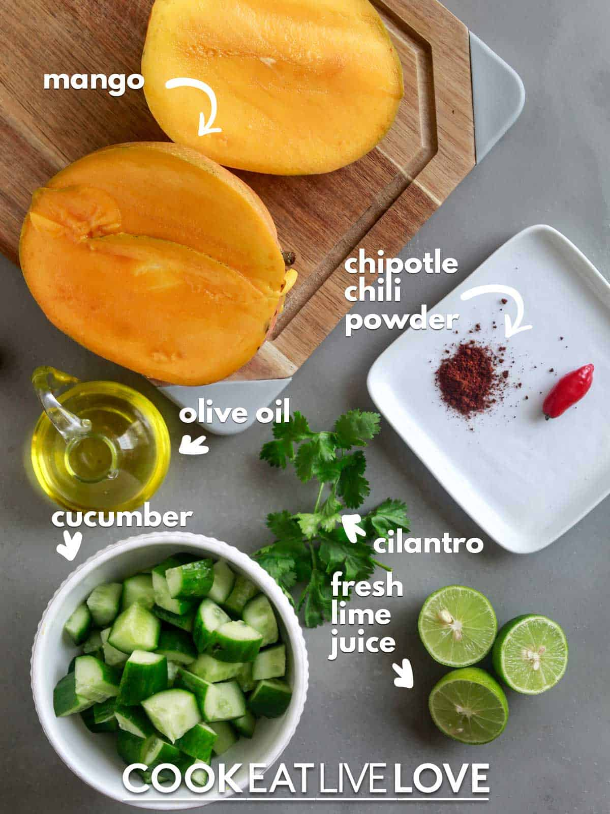 Ingredients to make mango cucumber salad on table with text