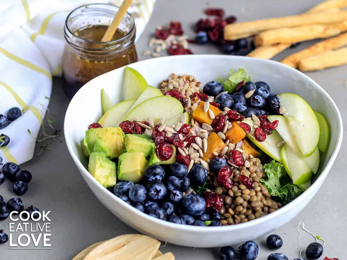 Nourish bowl all served up in white bowl with dressing and crackers