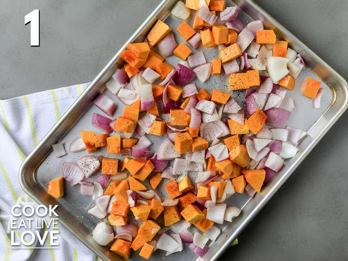 Butternut squash and onions on a baking sheet