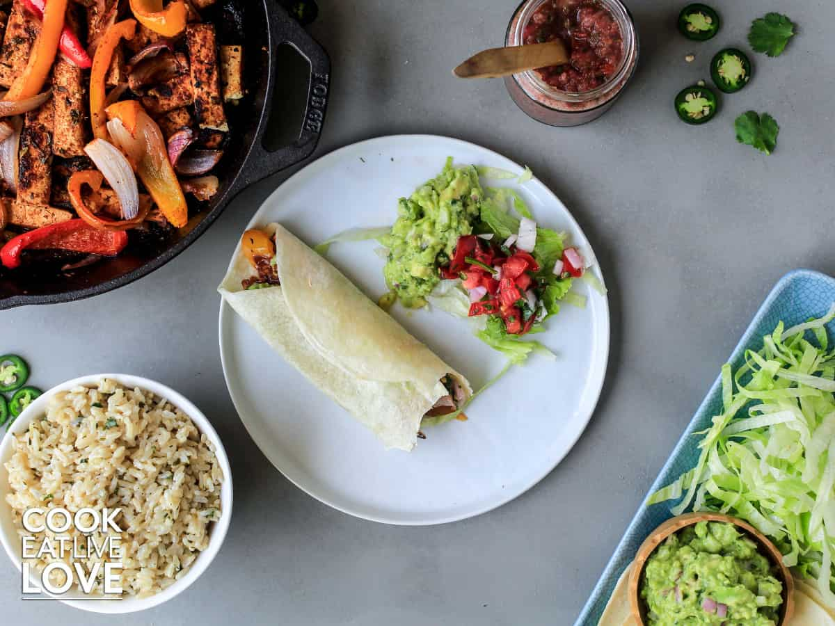 Fajita on a plate with various toppings and sides for fajitas around it
