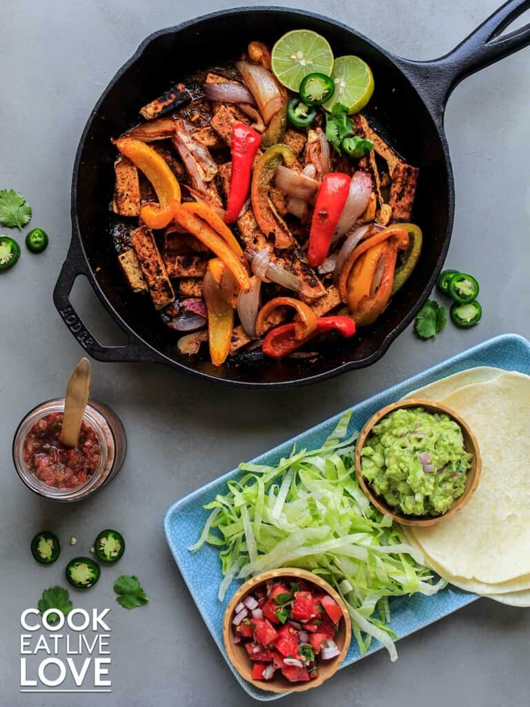 Tofu fajitas cooked in cast iron skillet with toppings and tortillas