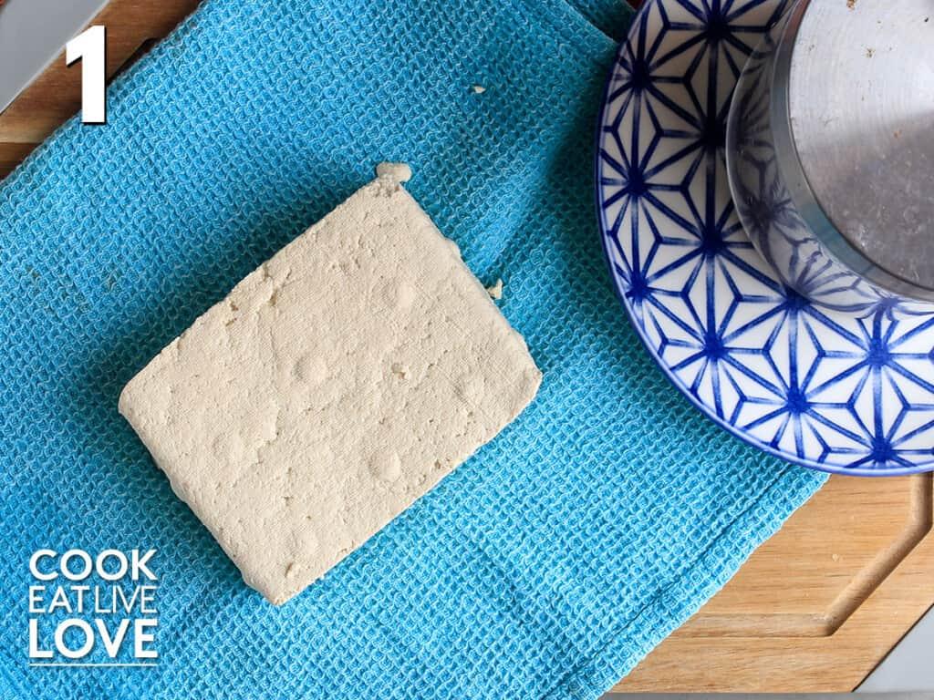 Opened tofu laying on a tea towel