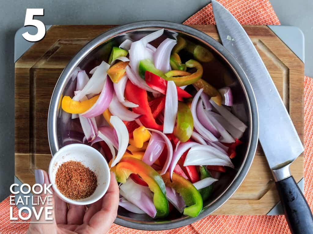 Adding the seasoning to the fajita veggies.