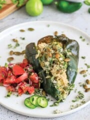 Vegetarian stuffed poblano pepper served up on a plate with pico de gallo