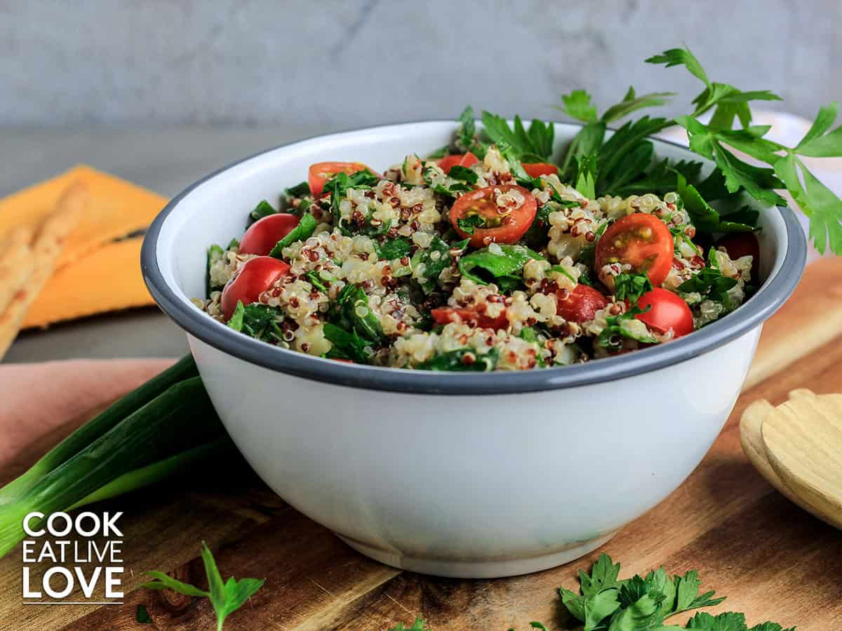 Zesty quinoa salad in a white bowl on a wooden cutting board