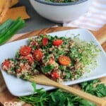 Zesty quinoa salad on a plate with a fork and fresh herb garnish