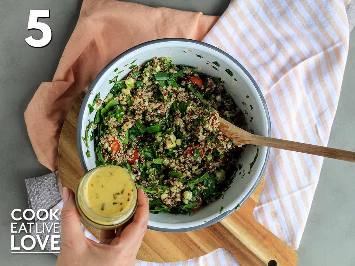 Adding the dressing to the zesty quinoa salad