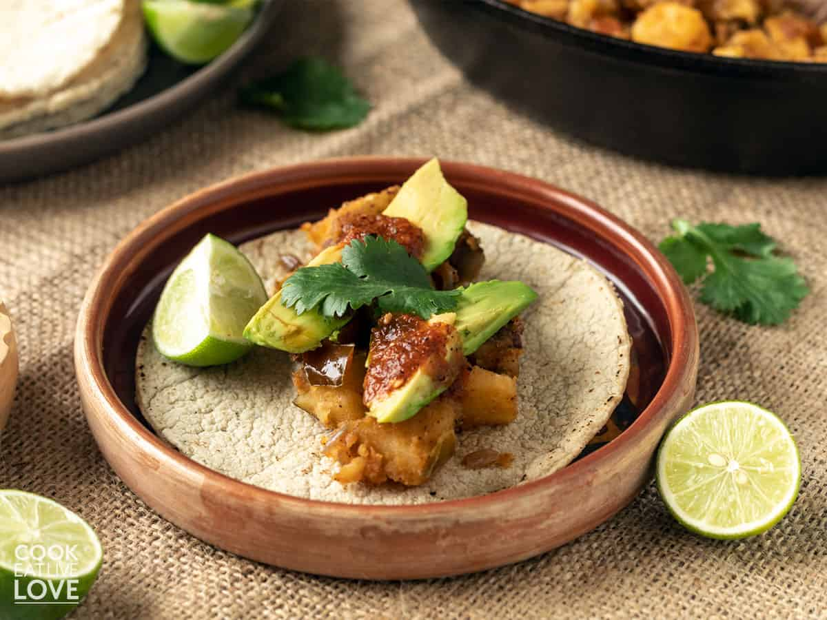 Potato tacos served up on a plate with avocado and salsa