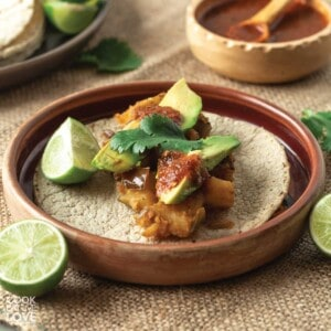 Potato tacos on a plate with limes and salsa