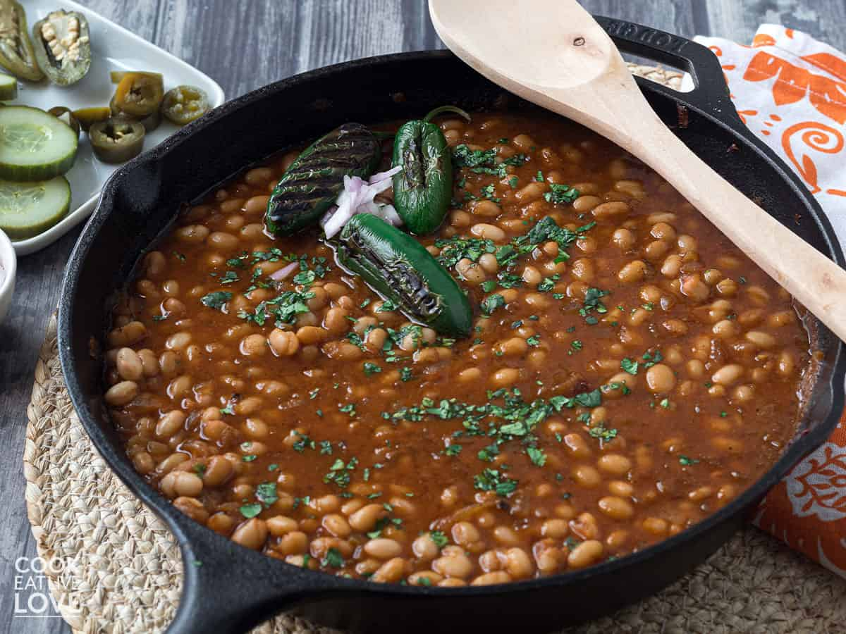 Vegan baked beans in skillet with wooden spoon