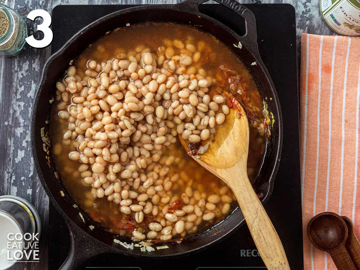 Beans and water are added to the skillet.