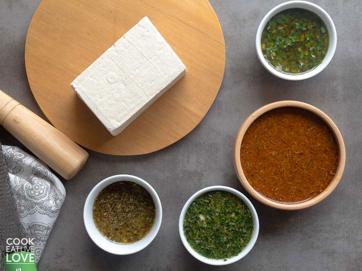 Block of tofu on a cutting board surrounded by bowls of tofu marinades