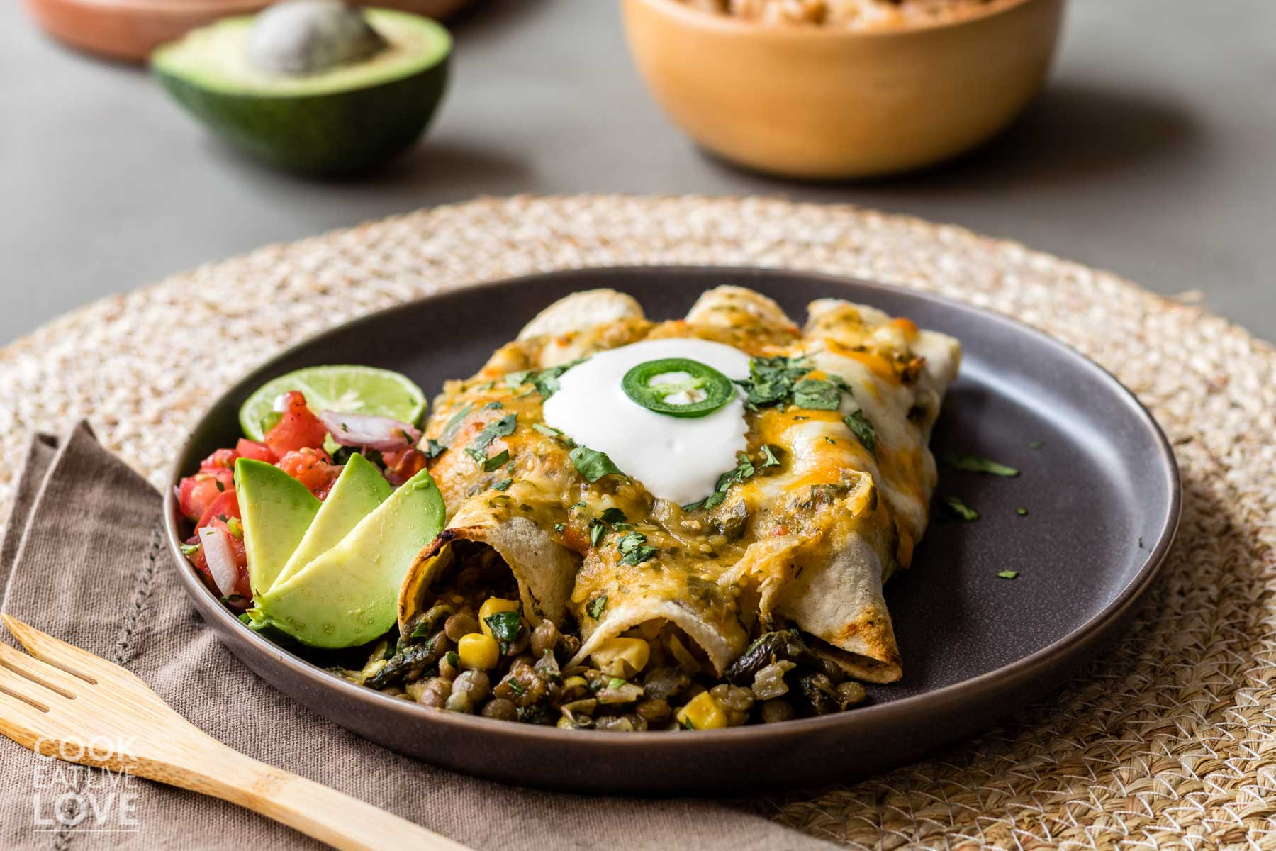 Three vegetarian green enchiladas on a plate with sour cream and a slice of jalapeno