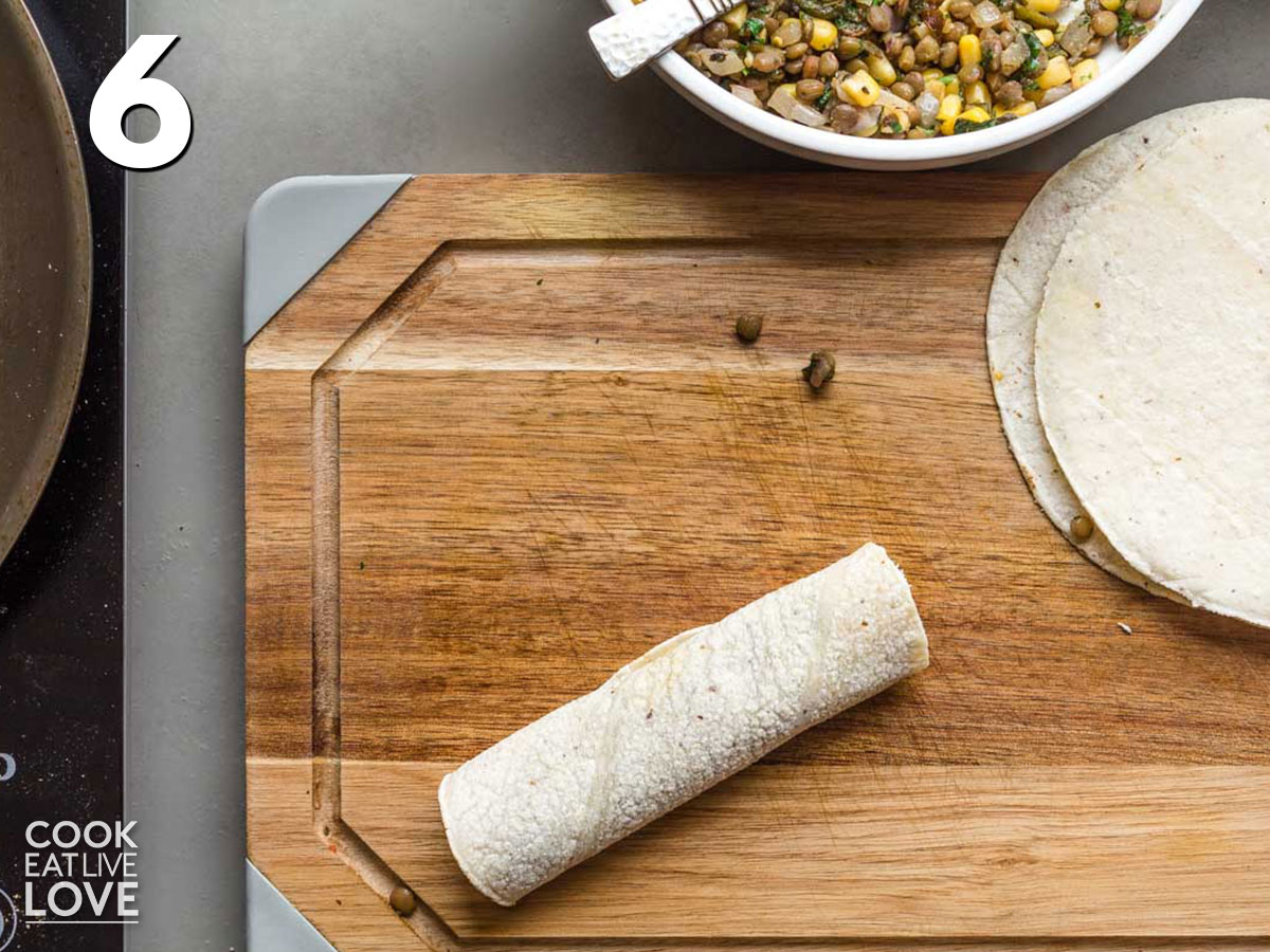 Tortilla is rolled to make an enchilada